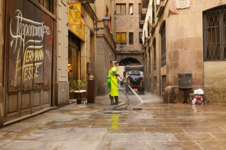 BARCELONA, SPAIN - JUNE 1: Wet cleaning of old streets in June 1, 2013 in Barcelona, Spain. Street cleaner cleaning  ancient district with water