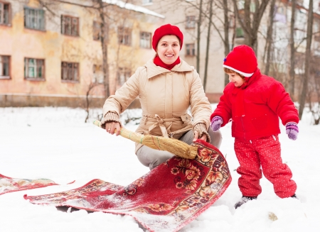 Smiling mother with daughter cleans rug with snow in winter day outdoor photo