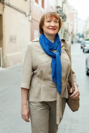 都市通りでスカーフを身に着けて成熟した女性の屋外のポートレート