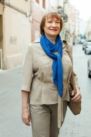Outdoor portrait of mature woman wearing scarf in city street photo