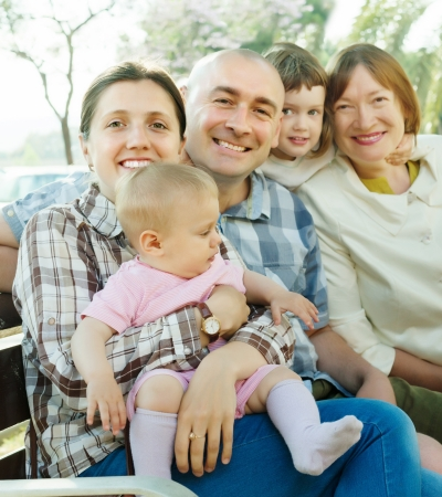 Outdoor portrait of happy multigeneration family on bench in summer park photo