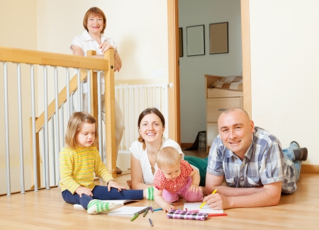 married couple with children and  grandmother in home interior together photo