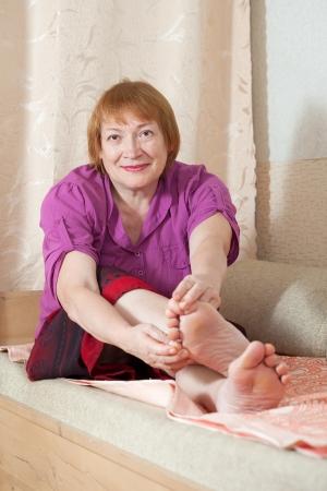 toenail fungus: Mature woman looks at her toenails Stock Photo