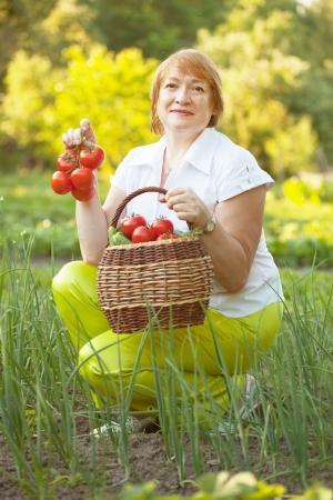 mature woman with vegetables in garden photo