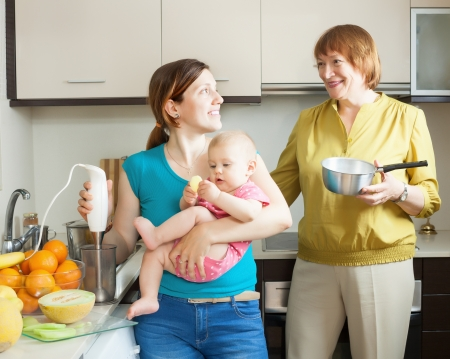 Happy family of three generations with blender cooking fruit puree  Stock Photo - 21234333