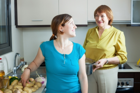 Happy women together  cooking   in kitchen at home Stock Photo - 21234334