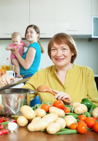 Mature woman for adult daughter with baby girl cooking lunch in kitchen photo