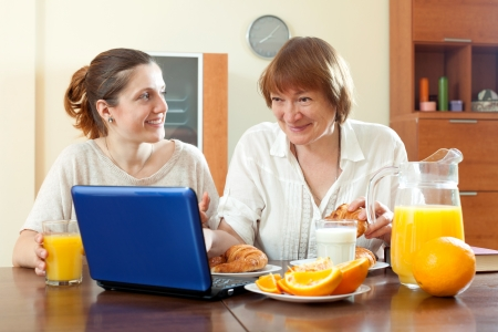 Mature mother and adult daughter  using laptop during breakfast