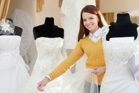 Smiling pretty bride chooses wedding gown at bridal boutique photo