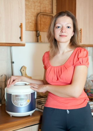 Woman with electric crock pot in her kitchen photo