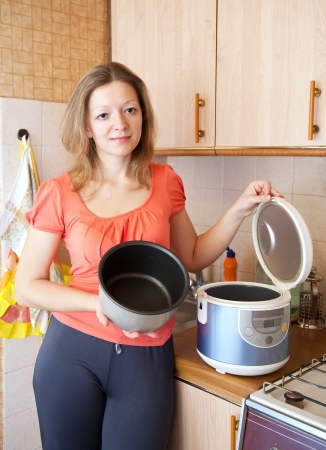 slow cooker: Young woman with slow cooker in her kitchen