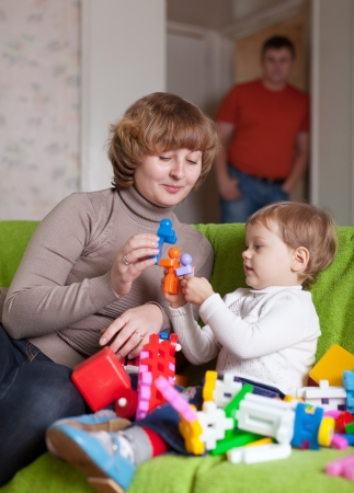 mother and child plays with toys in home photo
