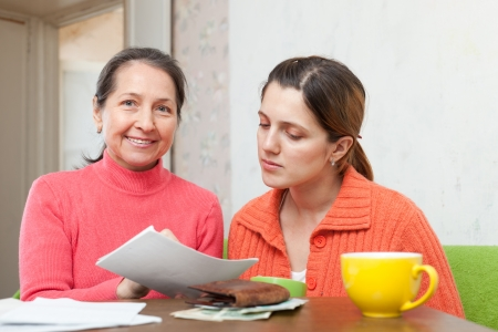 satisfied people: Mature mother helps adult daughter  to fills in  utility payments bills. Focus on mature Stock Photo