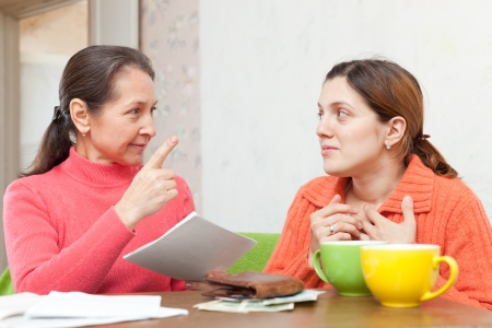Mature mother berates adult daughter for utility payments bills or credits photo