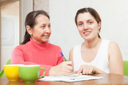 Two women fills in the questionnaire at  home photo