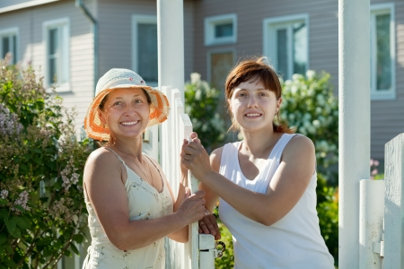poling: Two happy women talking near fence wicket