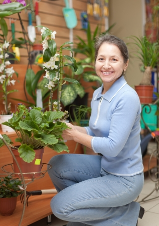 Mature woman with Dendrobium orchid  in flower store photo