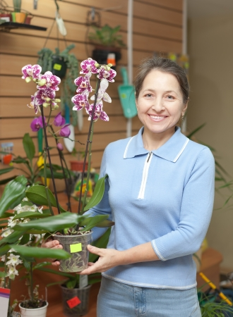 Happy mature woman with Phalaenopsis orchid in flower store photo
