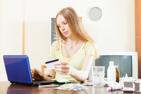 pensive woman buying medication online with laptop and card at home  photo