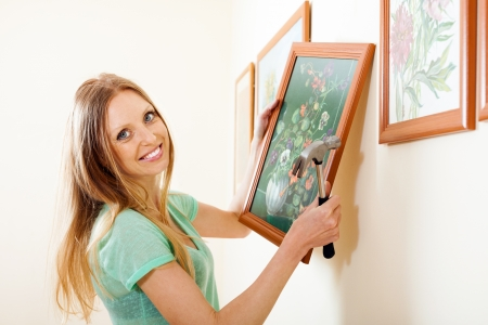 Happy blonde woman hanging  picture with flowers on wall at home photo