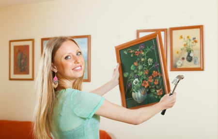 Young woman hanging the art picture on wall at home photo