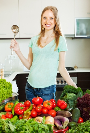 happy beautiful woman with vegetables  in home kitchen photo