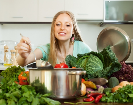 Long-haired housewife cooking fresh vegetables at home kitchen photo