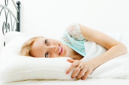 Blonde woman awaking on white sheet in her bed at home photo