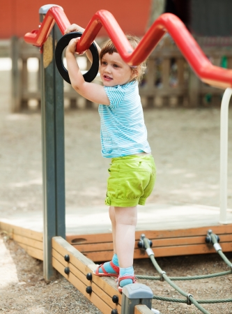 adroitness:   baby girl  at playground area  Stock Photo
