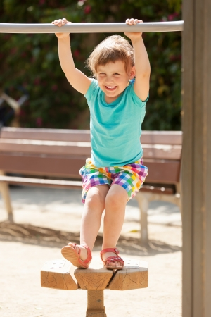 Laughing child  at playground  in sunny summer day  photo