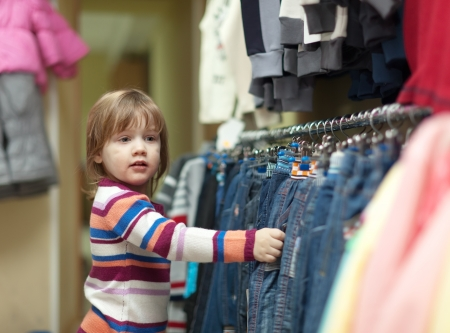 2 years child looking at jeans in clothes shop photo