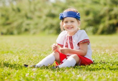 Smiling child in russian folk clothes on grass photo