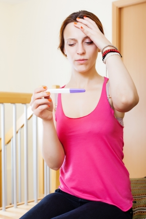 Sad seus  woman with pregnancy test at home inter Stock Photo - 21322722