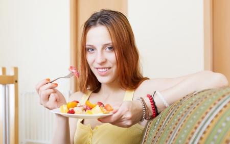 ordinary woman: red-hair ordinary woman eating fruits salad at home interior