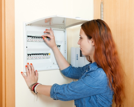 fusebox: woman turning off the light-switch in the hall Stock Photo
