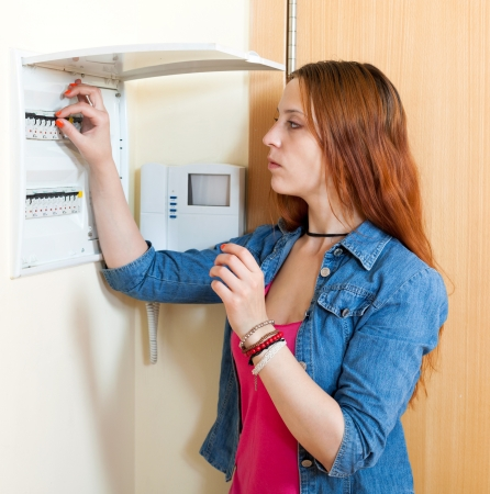 home automation: Sad cute woman near power control panel  at home