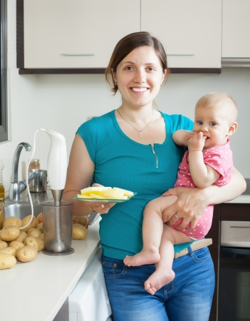 Young woman and baby girl cooking mashed potatoes with blender in kitchen Stock Photo - 21351019