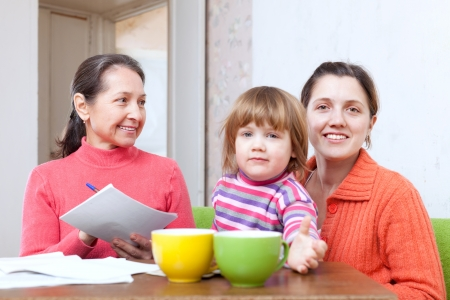 Mature woman and adult daughter with child is calculates the family budget at  home. Focus on adults Stock Photo - 21351033