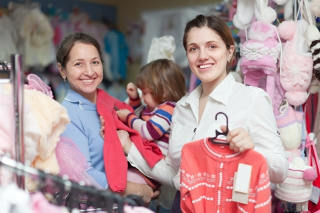 Two women and child chooses wear at clothes store. Focus on woman photo