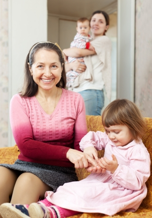 Two women with baby girls plays at home together photo