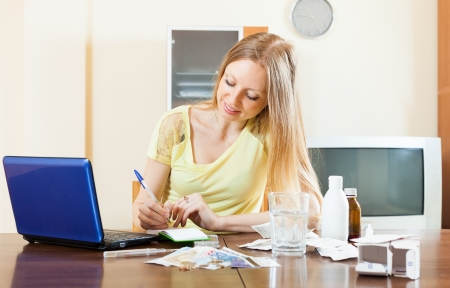 long-haired woman reading about medications on laptop in internet at home photo
