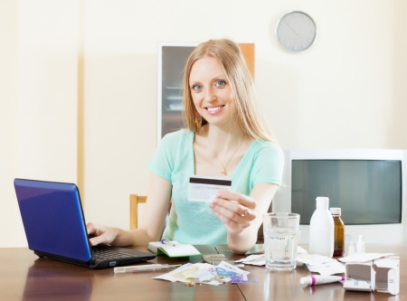 troche: beauty woman shopping medications on internet from home, using laptop and paying with credit card Stock Photo