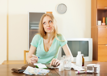 sickness sad woman counting the cost of treatment at home photo
