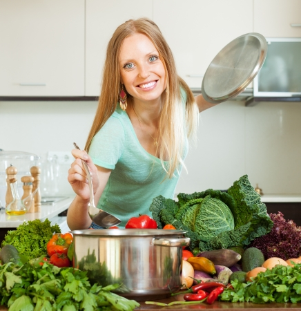 Long-haired woman cooking with ladle from raw vegetables in home kitchen photo