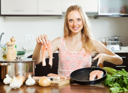 Smiling housewife cooking raw salmon at home kitchen  photo