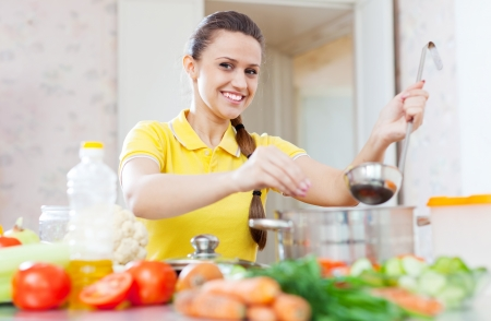 young add: Happy young woman salts the soup in the pan