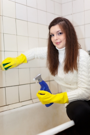 woman cleans bathroom with sponge at her home photo
