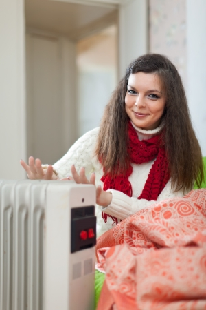 Smiling long-haired woman near oil heater in home