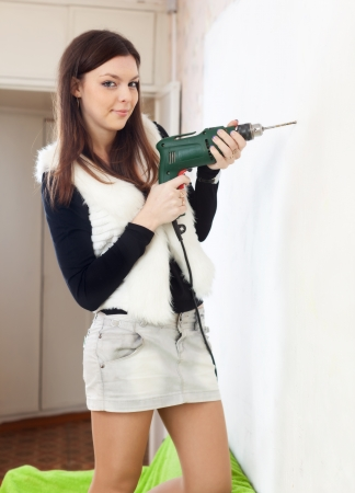modifying: Young woman makes repairs in the apartment