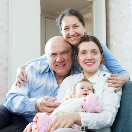 happy mature couple with daughter and granddaughter in home interior together photo